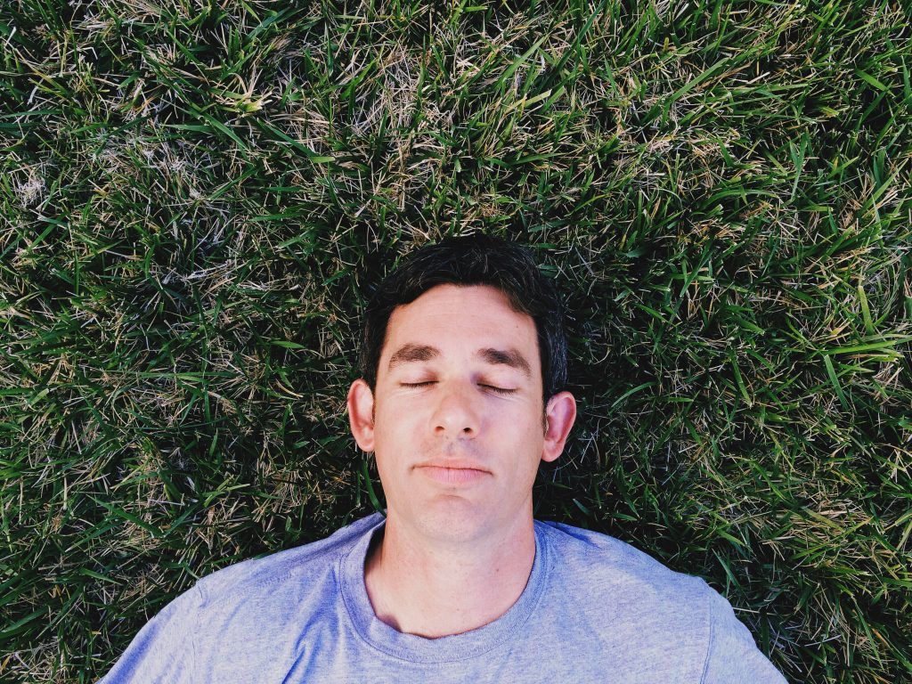 Dad daydreaming in the grass with no kids screaming in his ear.